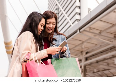 two young beautiful women using mobile phone or smart phone in modern city, shopping consumerism and people concept.