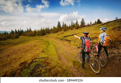 Two young bikers looking at the mountains