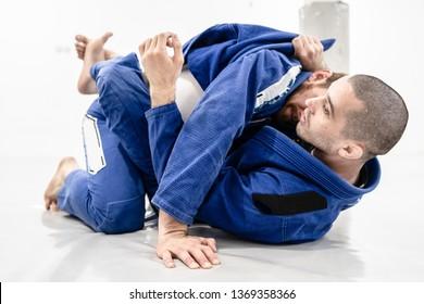 Two young BJJ Brazilian Jiu jitsu Athlete fighters training sparing technique at the academy fight lapel gi kimono