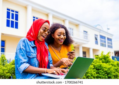 Two young black African female couples watching movies form Thier laptop . two friends browsing internet checking shopping website holding credit card