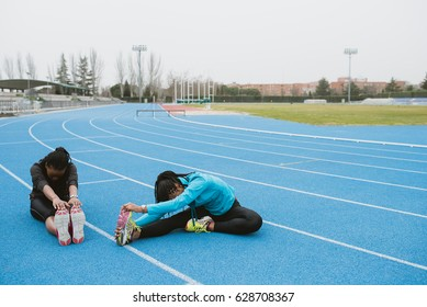 Two young black girls in sportswear sitting on race track and stretching.