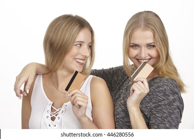 Two young blonde happy laughing girlfriends show their golden credit cards and talk about spending a lot of money. She bites into the plastic card.