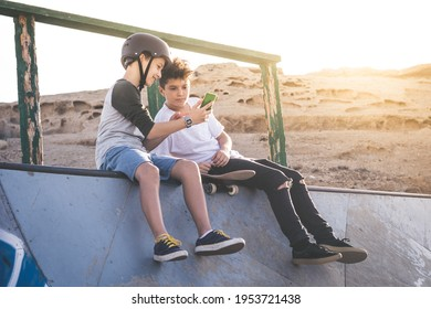 Two young boy using smartphone at the skate park, sitting on an halfpipe ramp. Teenagers communicate with friends with cell phone sharing video from skatepark. Youth, communication, new tech concept.