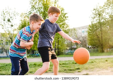 Two young boys chasing a basketball while practicing their game outdoors on a playing field in the warm glow of the sun