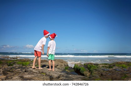Two young boys in christmas caps on the beach. Christmas near the ocean