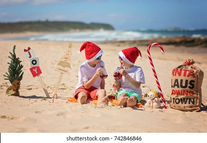 Two young boys in christmas caps sitting on the beach, ocean in background. Christmas on the beach
