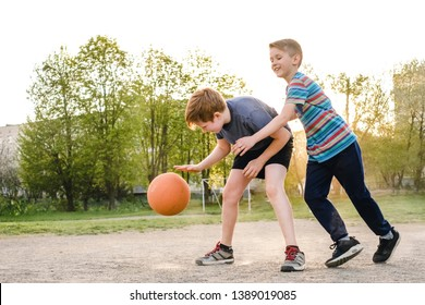 Two young boys enjoying a game of basketball challenging each other for the ball backlit by the bright flare of a warm spring sun behind their heads