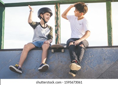 Two young boys hit high five after nice tricks and jumps at the skatepark. Trendy teenagers enjoying free time at the skate park, sitting on half pipe ramp. Youth, togetherness and friendship concept