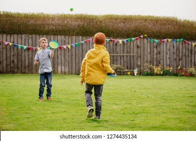 Two young boys playing outside in a back garden. They are throwing a tennis ball to each other and catching it with a velcro mitt.