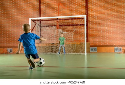 Two young boys playing soccer on an indoor court with one standing in the goalposts as the second prepares to kick for goal