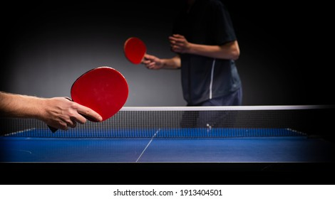 Two young boys playing table tennis, focus on racquet