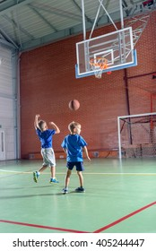 Two young boys practicing their basketball plying together on an indoor court shooting for goal