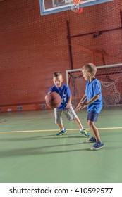 Two young boys practicing their basketball playing a game together on an indoor court as they bounce the ball below the goal post