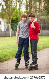 Two young boys rollerblading on a sidewalk