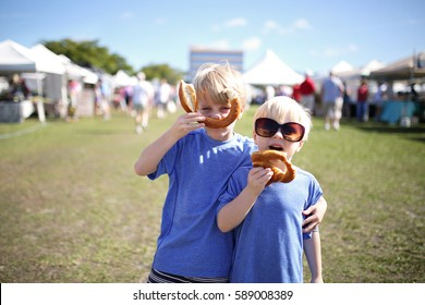 Two young boys: a seven year old and his little brother, are having fun eating pretzels and making funny faces at a farmer's market outside in Marco Island, Florida.