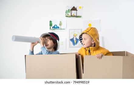 Two young boys standing inside of carton boxes, one of them is looking aside through rolled piece of paper. Childish drawings hanging on background