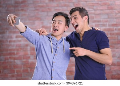 Two young  boys taking selfie with mobile phone on brick wall background