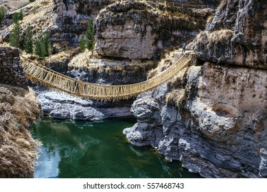 two young boys walking over a rope bridge in the andes / Queswachoca / andes / peru / south america
