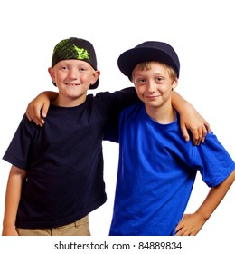 Two young boys who are friends with each other standing with their arms around each other smiling.