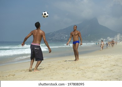 Two young Brazilian men playing beach football in Rio