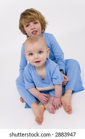 Two young brothers with blue eyes dressed in matching pyjamas