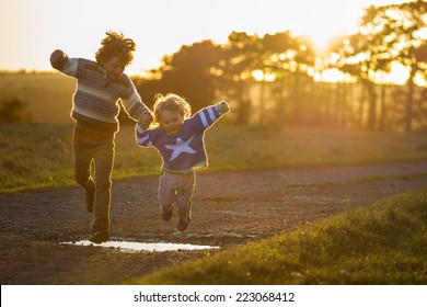 two young brothers holding hands and jumping over a puddle at sunset