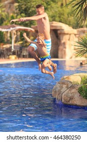 Two young brothers jumping into swimming pool