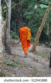 Two young Buddhist monks in saffron robes on a jungle trail,  Phnom Kulen, Cambodia