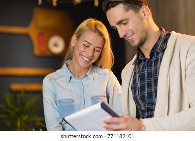 Two young business colleagues working together on paperwork
