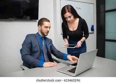 Two young business co-workers together in an office room