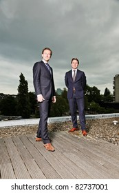 Two young business outdoors on top of building with cloudy sky.