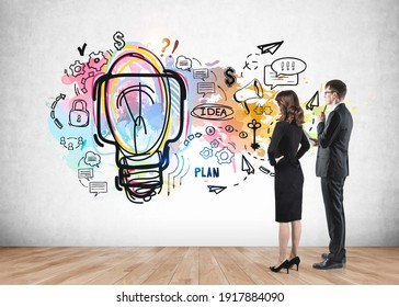 Two young business partners in office clothes thinking, looking at concrete wall with colourful business idea sketch drawn on it. Concept of brainstorming.