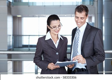Two young business people looking documents