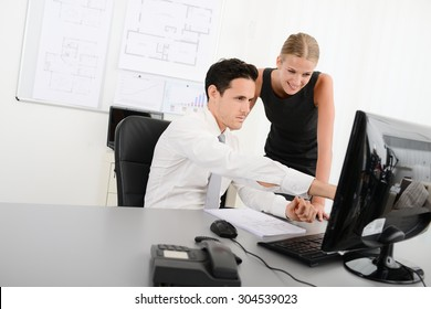 two young business people in office meeting and looking at data in computer