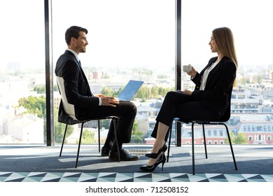 Two young business people sitting next to panoramic windows and talking