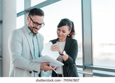Two young business people talking about documents in office lobby.