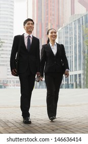 Two young business people walking outdoors, Beijing, China
