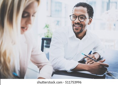 Two young business people working together in a modern office.Black man wearing glasses, looking at the businesswoman and smiling.Woman discussing with colleague new project.Horizontal,blurred