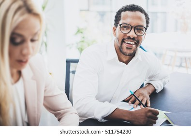Two young business people working together in a modern office.Black man wearing glasses, looking at the camera and smiling.Businesswoman discussing with colleague new project.Horizontal,blurred