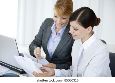 two young business woman or office workers discussing paperwork