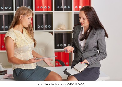 Two young business women  with computer tablet and daily log sit in the office.