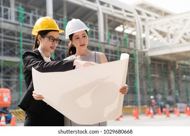 Two young business women industrial engineers in construction helmets building background and have a detail conversation. On a side view.