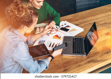 Two young business women sitting at table in front of laptop.On table is tablet computer and paper charts.First woman uses smartphone,other takes notes in notebook.Online education. Instagram filter.