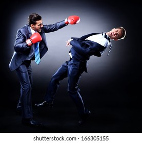 Two young businessman boxing againts dark background