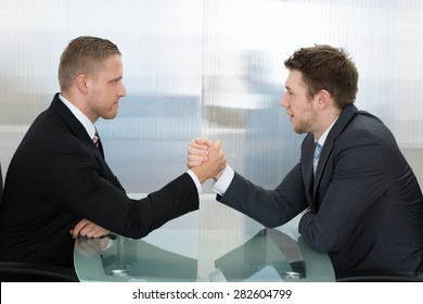 Two Young Businessman Holding Each Other Hands In The Office