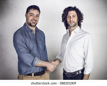 Two young businessman shaking hand