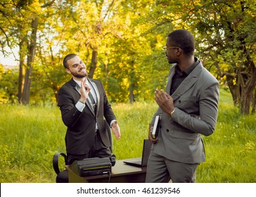 Two young businessman at work in the park. Beautiful background.