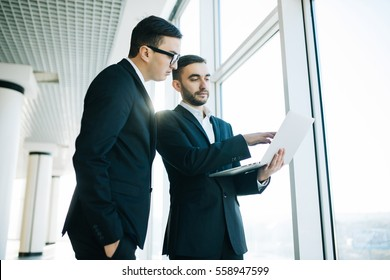 two young businessmen discussing project at meeting at office