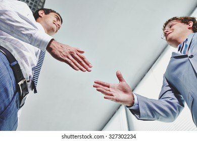 Two young businessmen greeting one another by handshake