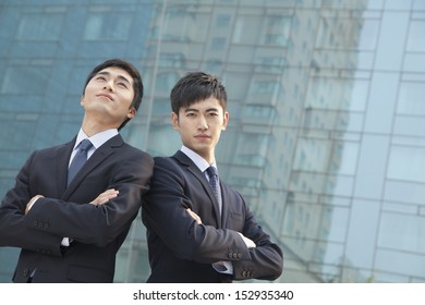 Two young businessmen outside glass building, portrait
